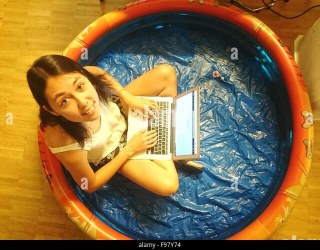 Portrait Of Woman Using Laptop In Wading Pool - Stock-Bilder