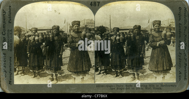 Dairymaids delivering milk in earthenware jars suspended on poles in Kief, Russia russians girls stereoview card - Stock-Bilder