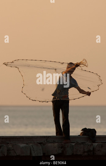 Boys trying to catch fish with a cast net as the sun goes down - Stock Image