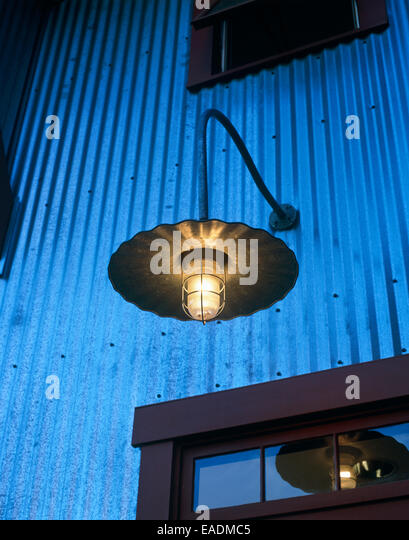 detail of contemporary country style outdoor light above entrance way at dusk - Stock-Bilder