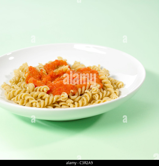 Whole-grain noodles with tomato sauce on green background - Stock-Bilder