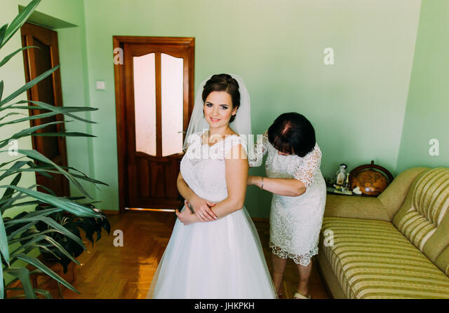 Happy mother assisting bride dressing up in hotel room before wedding ceremony - Stock Image