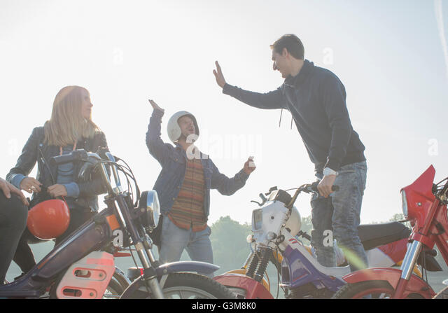Group of friends sitting on mopeds, two men giving high five - Stock Image