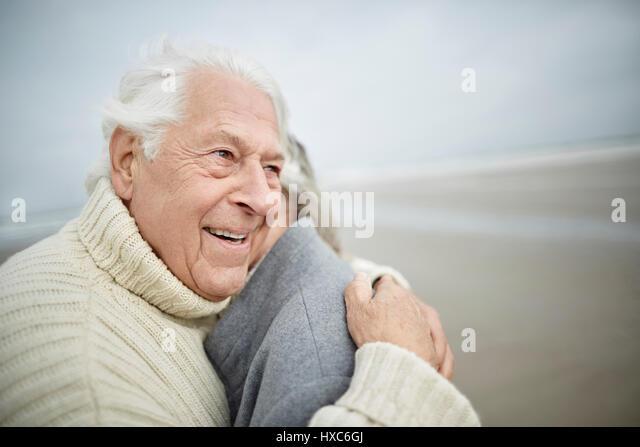 Affectionate senior couple hugging on winter beach - Stock Image