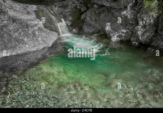 Crystalline water of a waterfall surrounded by gray rocks, Val Vertova near city of Bergamo - Stock Image