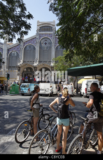 Group of young people with bicycles in front of Central market hall , Mercado Central, Valencia, Spain - Stock Image