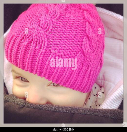 Smiling baby girl in pink hat in winter - Stock Image
