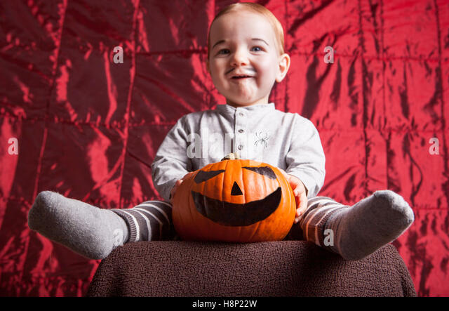 Smiling little boy dress up for halloween party. Red satin background - Stock Image