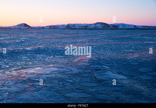 Pancake ice at sunset, Gulf of St. Lawrence, near Îles de la Madeleine (Magdalen Islands), Quebec, Canada. - Stock Image
