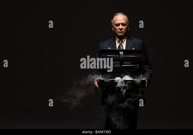 Businessman with smoking briefcase - Stock Image