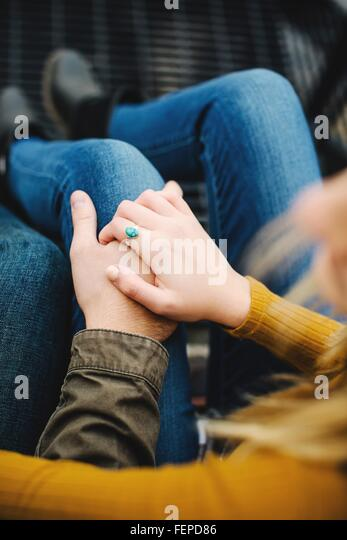 Over shoulder cropped shot of young couple holding hands on stairway - Stock Image