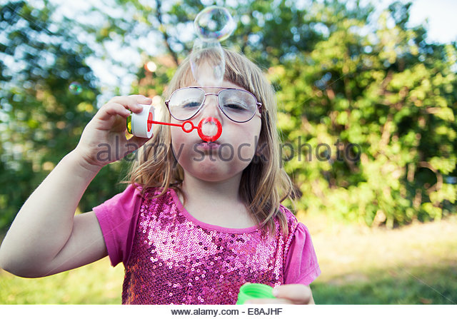 Close up of girl concentrating on blowing bubbles in garden - Stock Image