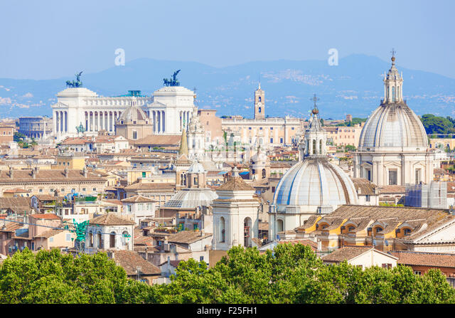 view of churches and domes of the rome skyline showing victor emmanuel II monument in the distance Rome Italy roma - Stock Image