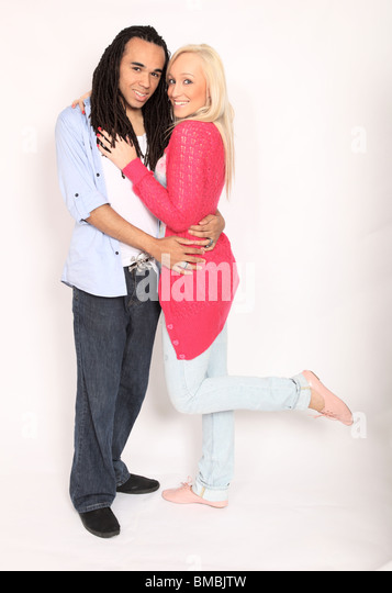 Happy young couple, mixed race, she has long blonde hair he has dreadlocks. Cut out. - Stock Image