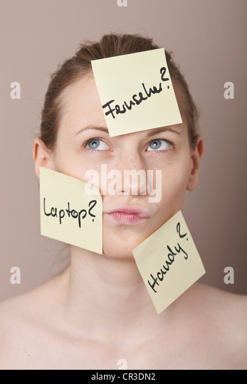 Post-It notes written in German with buying options, sticking to the face of an indecisive young woman - Stock Image