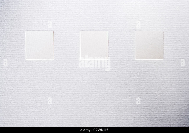 Squares cut in textured white paper - Stock Image