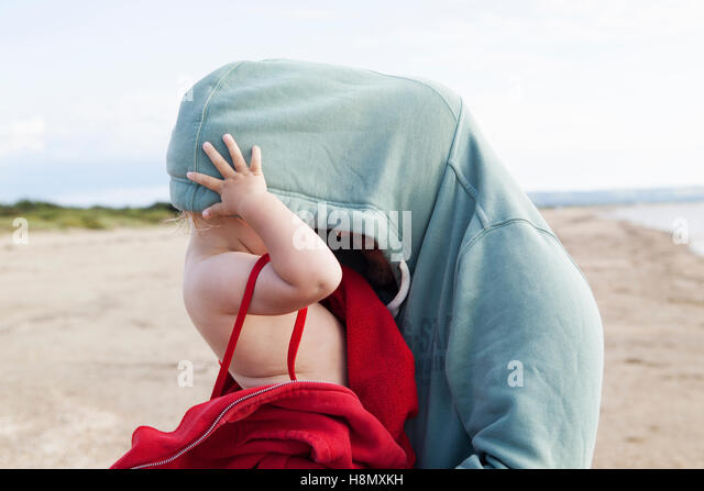 Girl (2-3) hiding in father´s hooded shirt - Stock Image