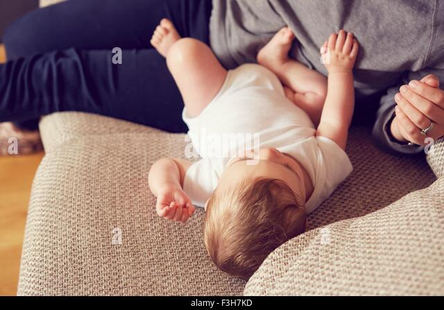 Mother and baby boy playing in living room - Stock Image