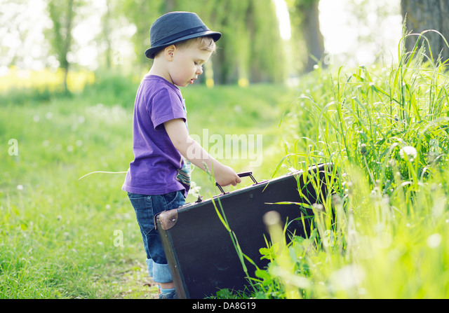 Photo of small child trying to escape with suitcase - Stock Image