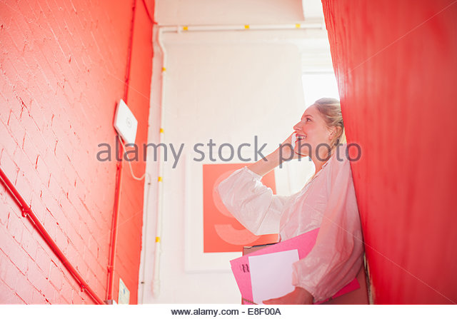 Smiling businesswoman holding folders and talking on cell phone in stairwell - Stock-Bilder