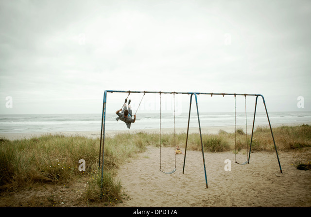 Female toddler watching father on beach swing - Stock Image
