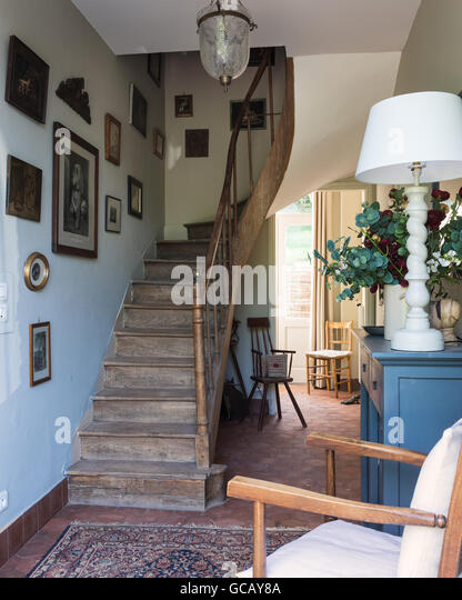 Entrance hall with terracotta floor tiles, wooden staircase and oriental rug - Stock Image