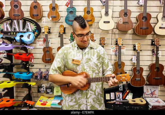 Hawaii Oahu Hawaiian Honolulu Hilo Hattie shopping sale display retail man playing ukulele - Stock Image