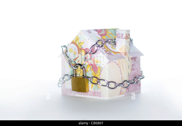 Model house folded with British pound banknotes chained and padlocked - Stock-Bilder