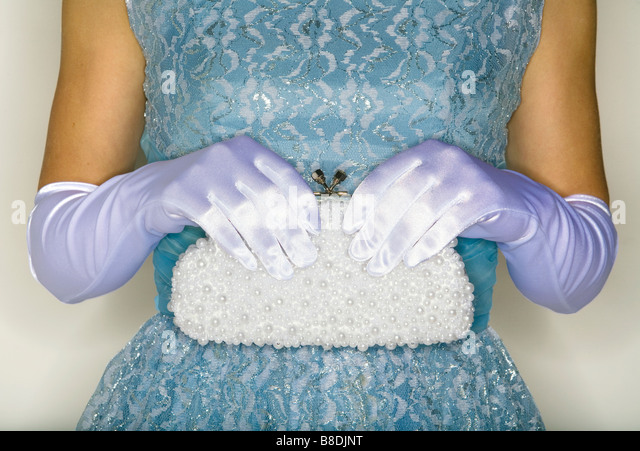 Gloved hands hold white handbag - Stock Image