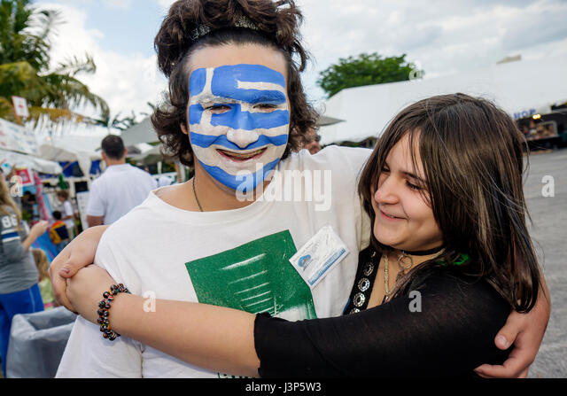 Miami Miami Florida Kendall St. Andrew Greek Orthodox Church Greek Festival boy girl teens couple Greece flag painted - Stock Image