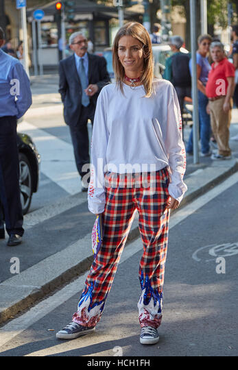 Woman with red and black checkered trousers before Jil Sander fashion show, Milan Fashion Week street style on September - Stock Image
