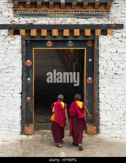 Two Buddhist monks walk into the entryway of the bridge into the Punakha Dzong in Punakha, Bhutan. - Stock Image
