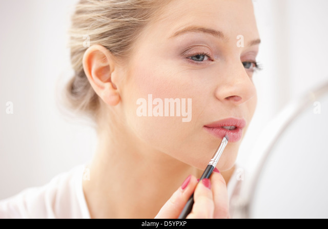 Woman Applying Lipstick with Makeup Brush - Stock Image