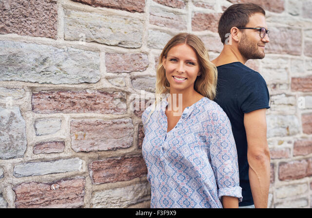 Couple standing back against each other against a wall - Stock-Bilder