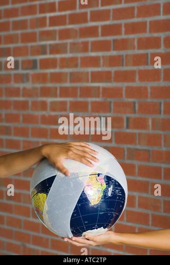 Hands holding a bandaged globe - Stock Image