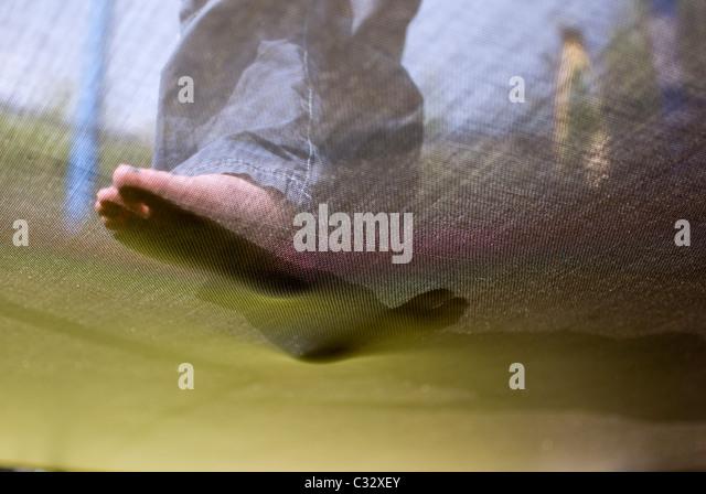 Underneath of feet on trampoline,foot, bare, foot, sole, step,abstract,feet on trampoline,verruca,foot hygene - Stock Image