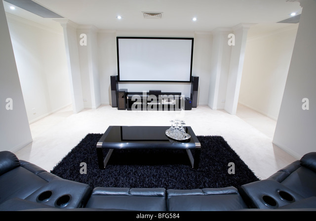 home theater room with black leather recliner chairs, black rug and table with wine glasses - Stock-Bilder