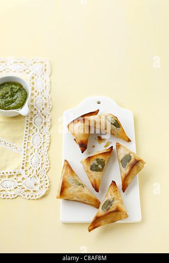 Small pesto filo pastry triangular pies - Stock Image
