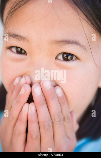 american girl covering mouth and feeling embarassed - Stock Image