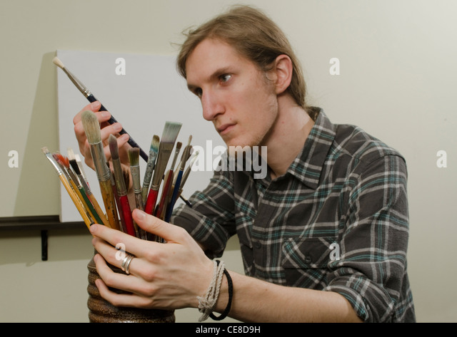 artist with brushes and blank canvas - Stock Image