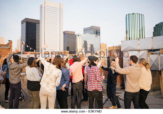 Crowd dancing at urban rooftop party - Stock Image