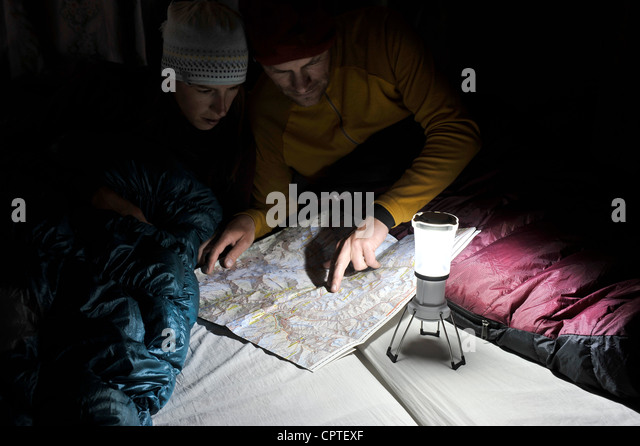 Couple in sleeping bags, looking at trail map, Yak Kharka, Nepal - Stock Image