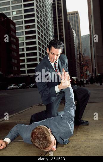 Businessmen fighting in street - Stock Image