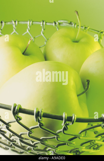 Golden Delicious Apples in Wire Fruit Bowl - Stock Image