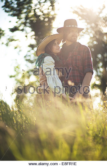 Couple wearing cowboy hats standing in field of long grass - Stock-Bilder