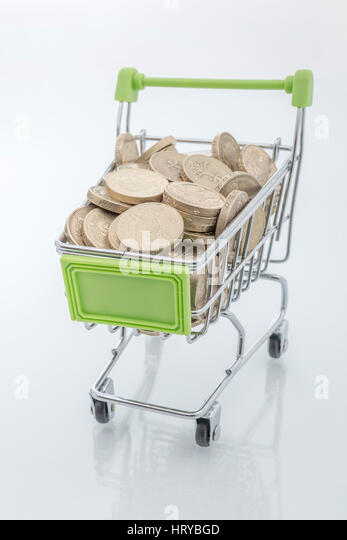 Pound coins in shopping basket / trolley. Representing UK consumer spending power and high street sales. - Stock Image
