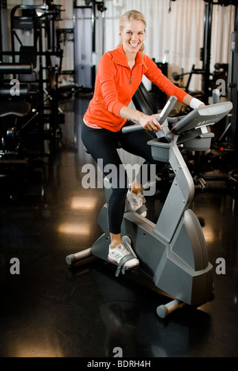 A woman doing indoor cycling at a gym - Stock Image