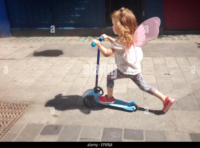 UK, England, London, Portrait of girl (2-3) with fairy wings riding scooter on city pavement - Stock Image
