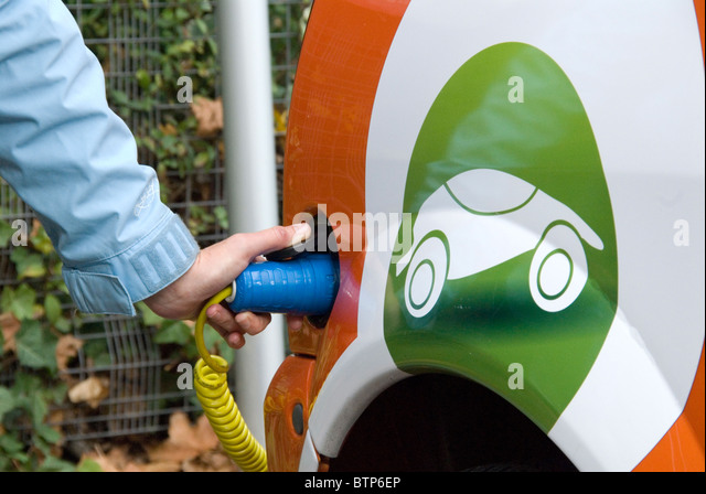 Woman plugging in an electric car rented from GoGo Electric Cars free EV Elektrobay charging point Sainsbury's supermarket - Stock Image