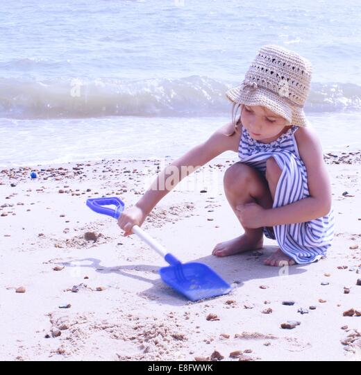Girl crouching on beach playing with plastic spade - Stock Image